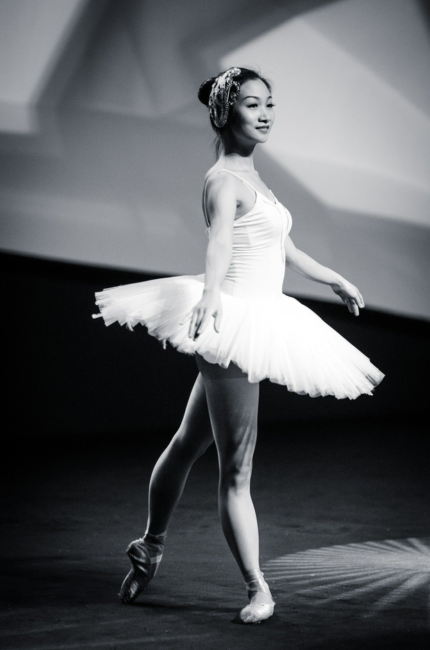 Black and white photo of woman wearing a white tutu, pointe shoes, and a decorative headpiece. Her arms are outstretched by her sides, and her left foot is extended behind her in the pointed tendu position.