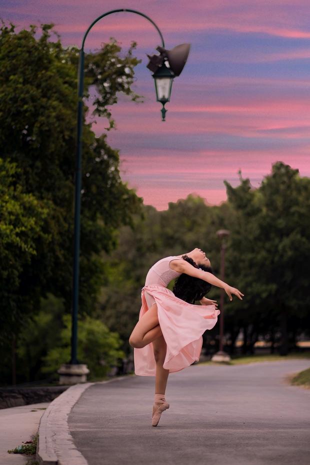 Ballet dancer on road beside streetlamp during sunset