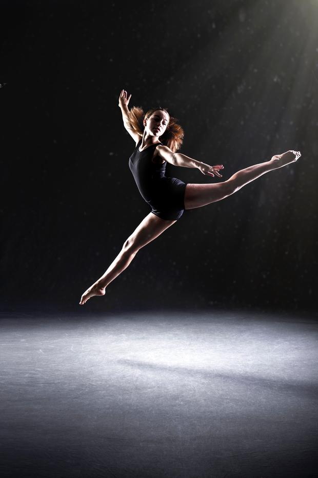 woman doing ballet against black background