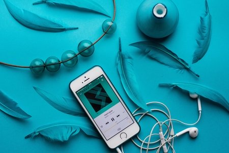 iPhone with EarPods besides blue feathers on a blue table.
