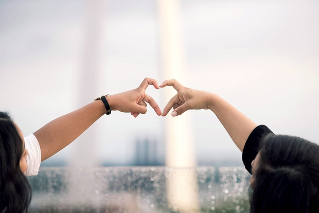 two different people's arms reach out in front of the St. Louis arch, their pointer finger and middle fingers coming together to make a heart