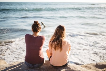 two women sit at the edge of the ocean facing the water