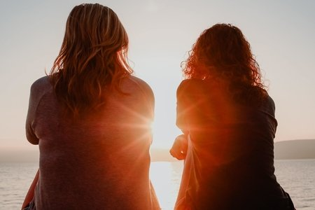 two women sit on the beach, facing the ocean. the sun shines in between them.