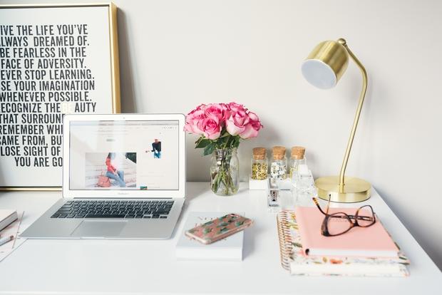 laptop, notebook, desk lamp, flowers on a desk