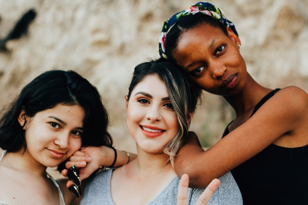 Three diverse women posing for a photo together leaning on eachother