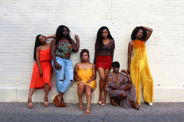 six black women standing and sitting agaisnt a white wall