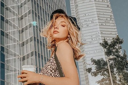 Katie Parsons wearing cheetah print in front of a skyscraper