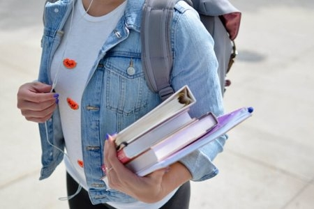 Person in denim shirt holding books