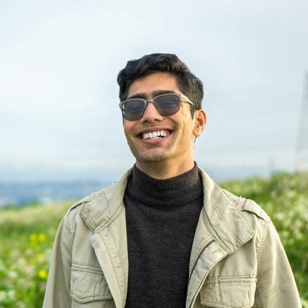 boy with glasses wearing black turtleneck and beige jacket