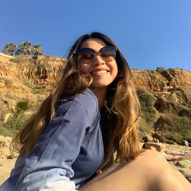 girl at the beach with sunglasses and blue shirt