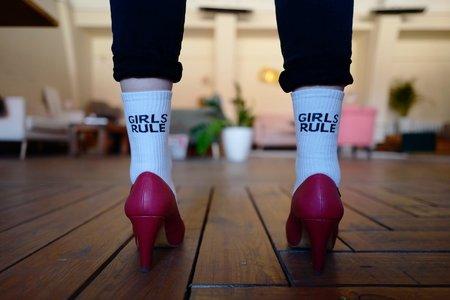Person wearing white Girls Rule socks