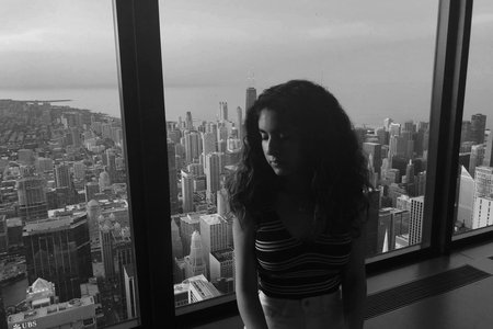 a B&W photo of a girl sitting on a window ledge with the skyline in the background