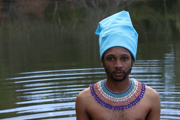 A Xhosa man, in traditional attire, stands infront of a body of water.