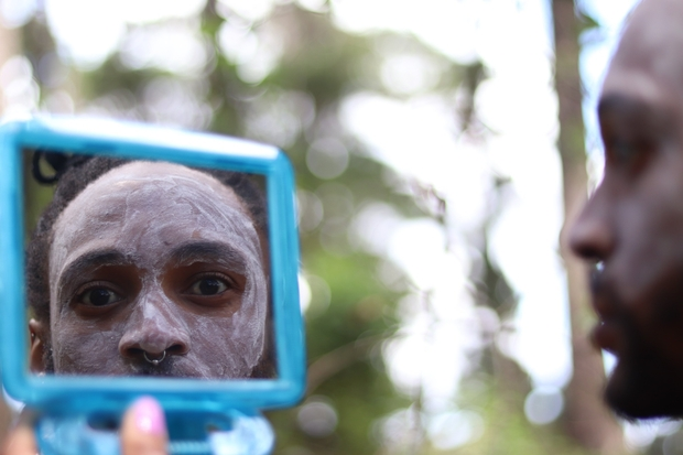 A Xhosa man, wearing traditional face paint, looks in a mirror.