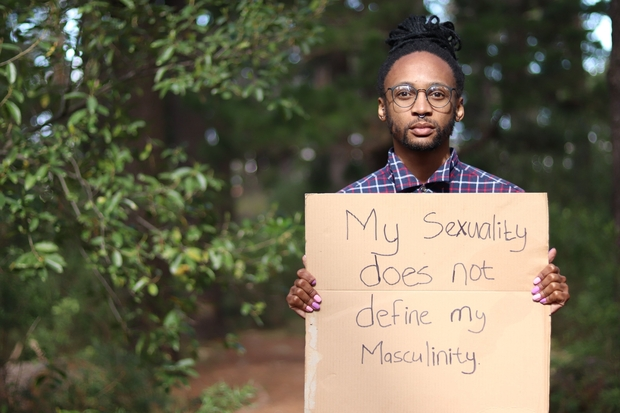 A Xhosa man holding a sign that says,