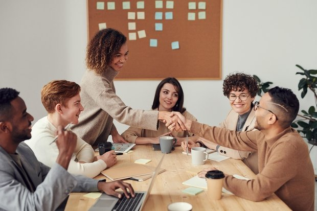 A group of people are in a meeting. They appear to be in a conference room at work. A woman is standing and shaking hands across the table with a man who is sitting down.