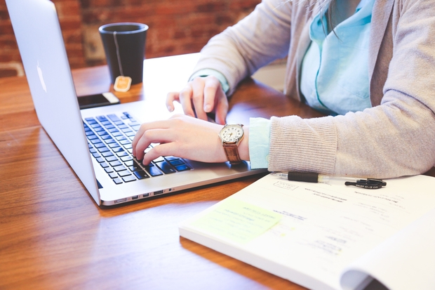 a person is seen sitting at a table, from the neck down. they are typing on a laptop and have a mug with tea and a highlighted book open next to them