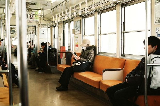 Masked person sitting on subway train car