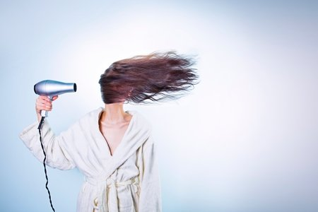 Girl with a hairdryer blowing her hair across her face
