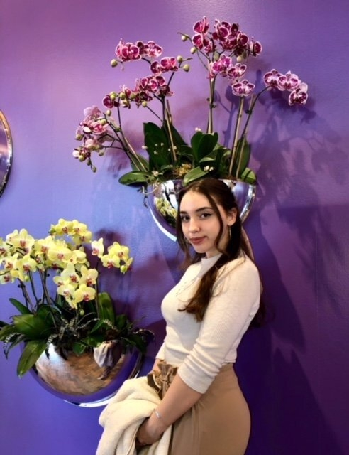 Girl smiling slightly, in front of purple and yellow orchids on purple wall