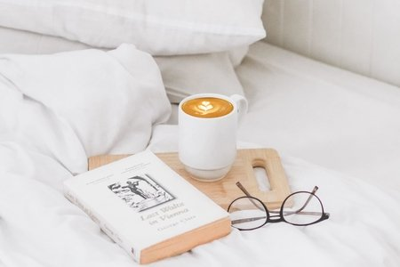 a bed with some books and a coffee