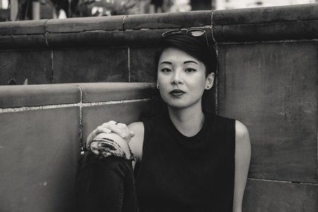 grayscale photo of Asian woman sitting at the corner of wall