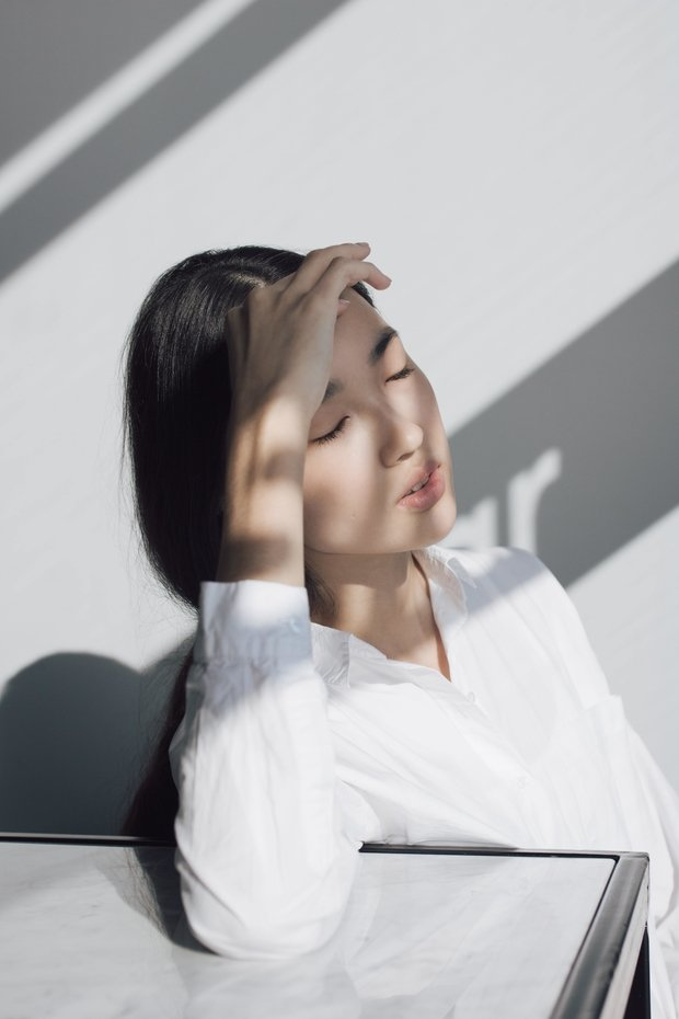 Asian woman leaning on white table