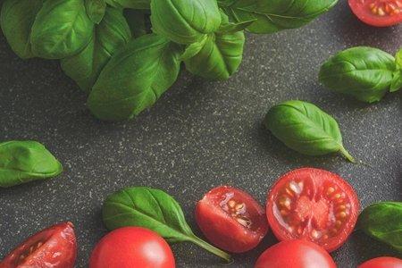 Tomatoes near basil leaves