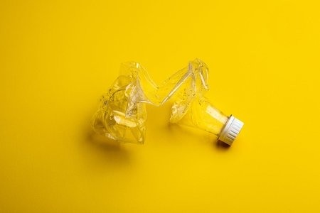 plastic bottle crushed against yellow background