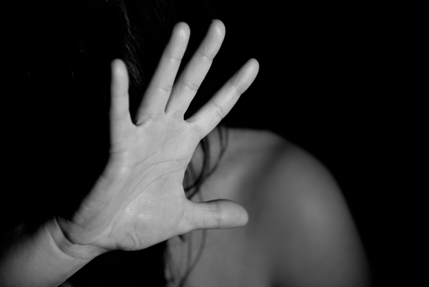 woman with her hand up to cover her face