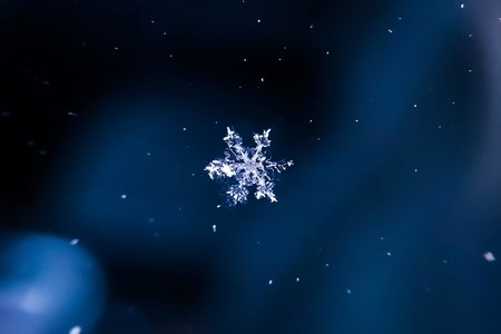 a design of a snowflake against a dark blue background