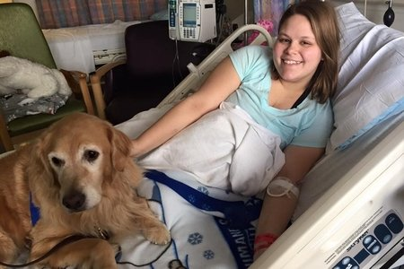 woman sitting in a hospital bed with a service dog
