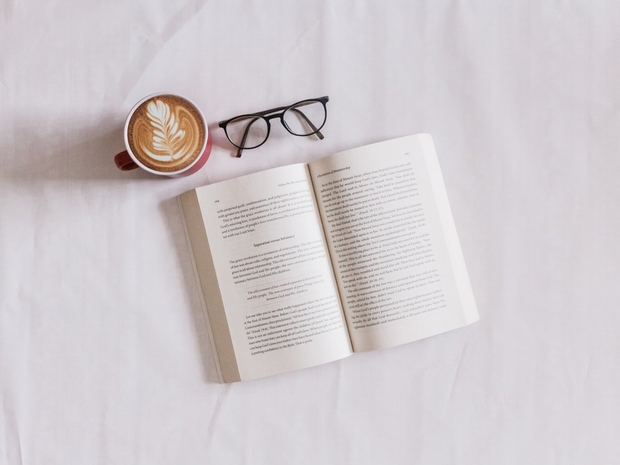 A pair of glasses, tea, and a book on a white surface