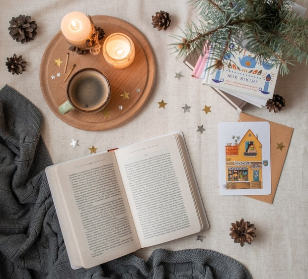 A candle, books, and a mug upon a white surface