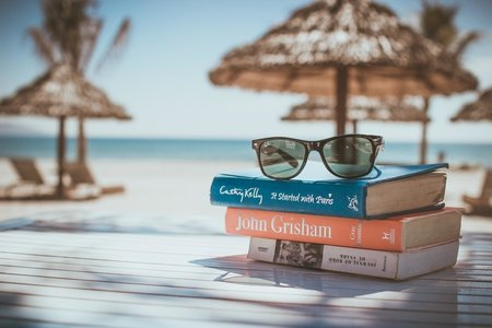 Books stacked in front of a beach