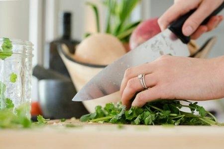 Hands chopping cilantro