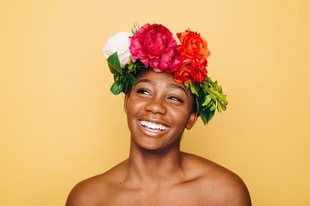 African american woman smiling against yellow background wearing flower crown