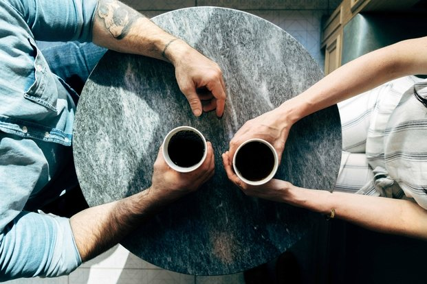 Top down picture of man and woman holding coffee cups