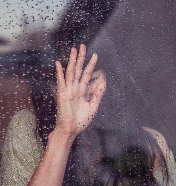 Woman touches rainy window