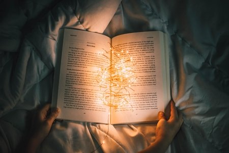 Person holds string lights inside of book