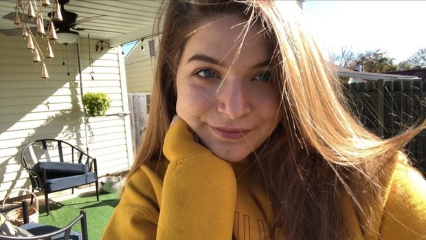 selfie of woman in yellow sweatshirt