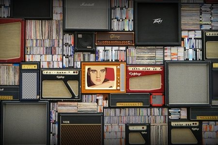 Various speakers and musical records. Image of Elvis Presley centered.