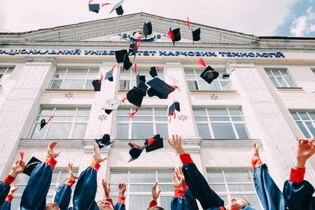 graduation caps in air