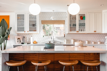an island in a kitchen with a breakfast bar. there is a window over the sing and glass-fronted cabinets. the walls are white hexagonal tiles and there is an orange accent