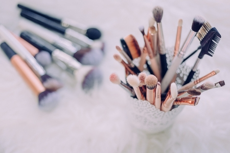 a cup of makeup brushes is in focus on the right, and a small handful of brushes lays out of focus on the table to the left