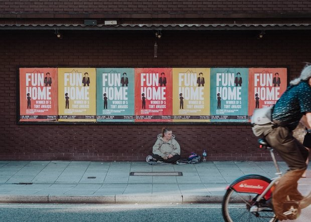 Person sitting on street underneath Fun Home posters