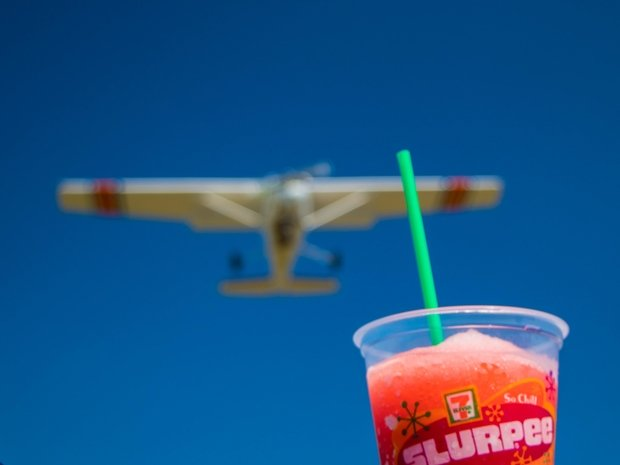 7-Eleven slurpee cup with airplane in background