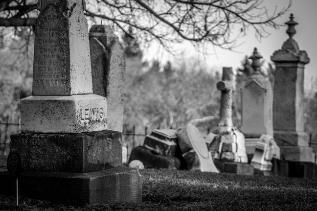 grayscale photo of tombstones in a graveyard