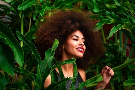 Woman with afro surrounded by plants
