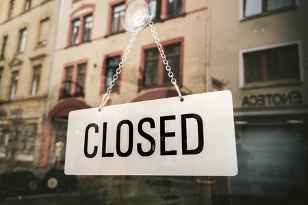 """A white sign that says """"Closed"""" in a window reflection"""